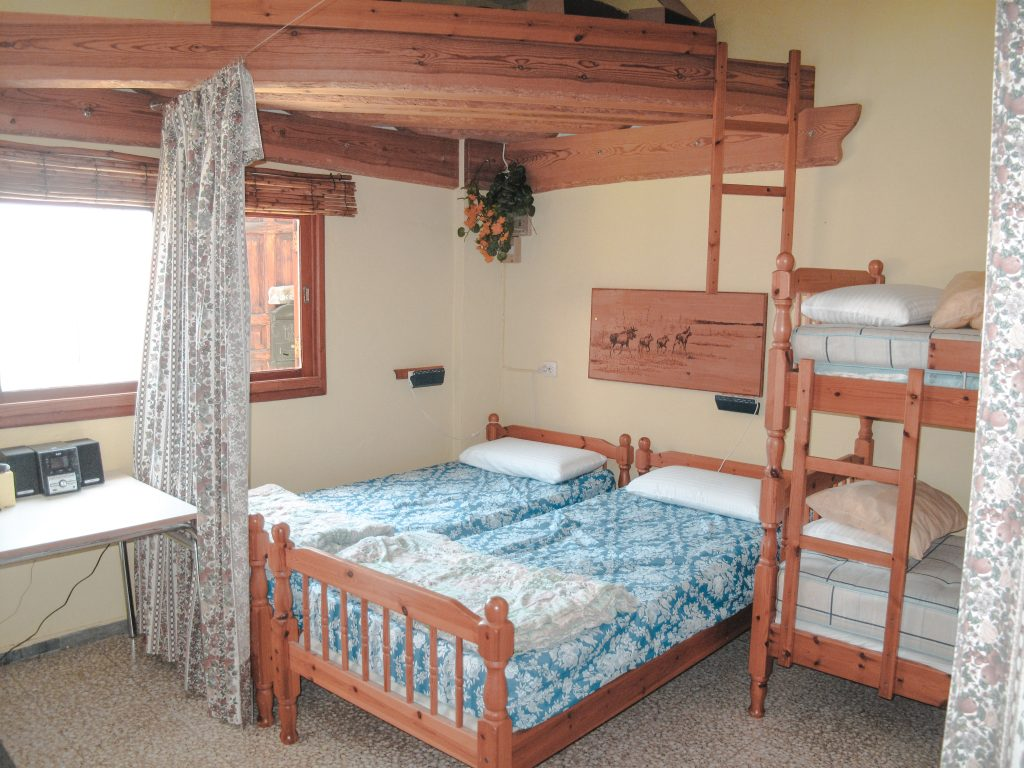 Two bed next to each other and a bunk bed.